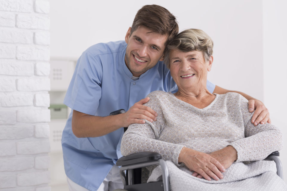 A home health provider in blue scrubs and a happy patient smile together.