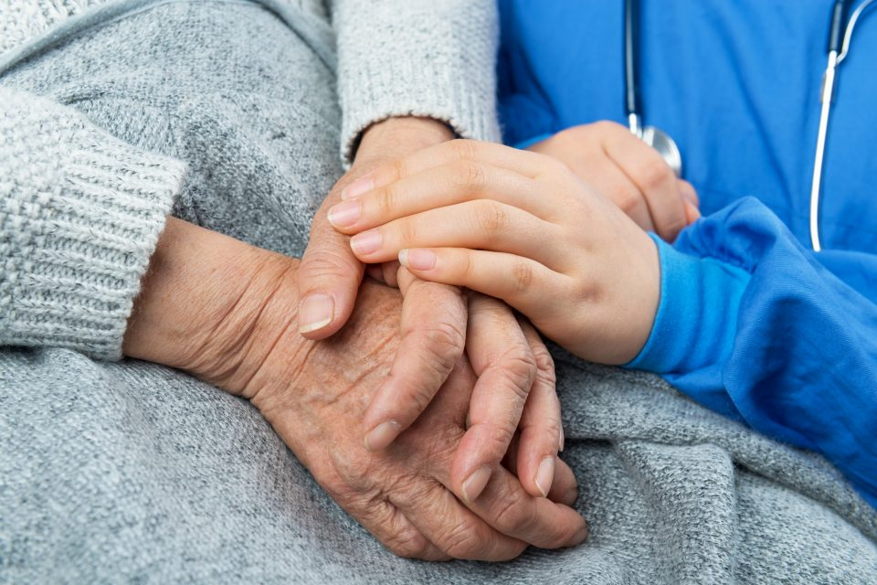 An elderly hospice patient in a gray sweater holds hands with a care provider.